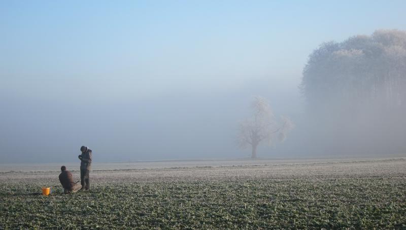 Zwei Personen auf einem winterlichen Agrarfeld, Nebel im Hintergrund